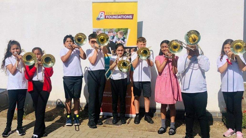 Line of children holding brass instruments, standing in front of a yellow Brass Foundations banner