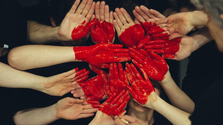 Many red painted hands placed together to form a heart shape