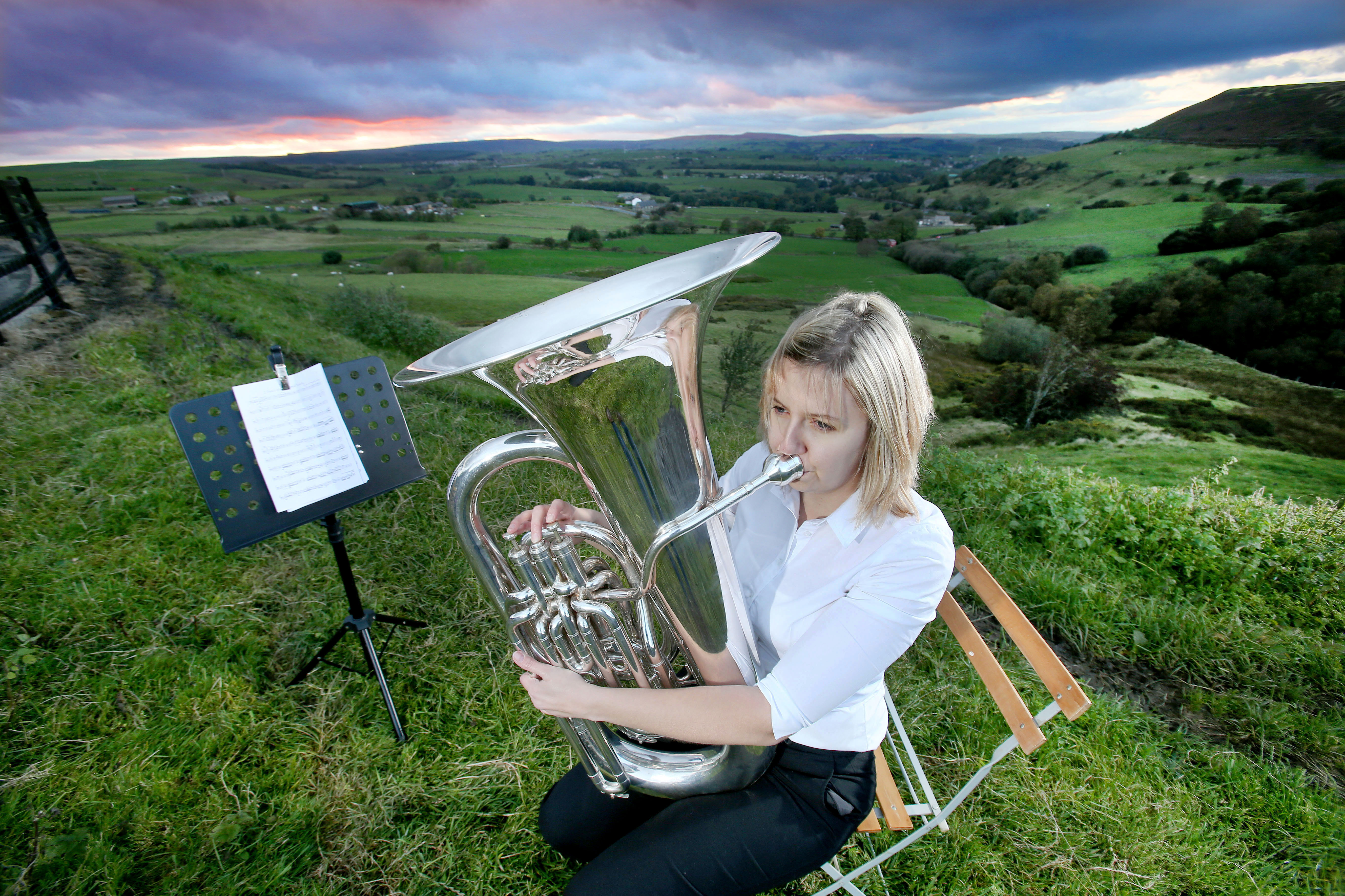 Woman playing a bass on top of the moors