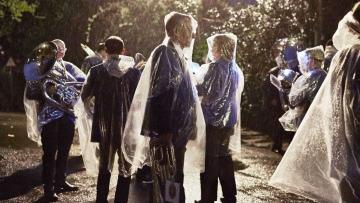 Group of musicians standing in the rain at dusk, wearing transparent rain ponchos