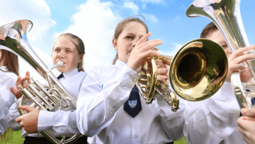Two girls and a boy playing silver brass instruments in front of a bright but cloudy sky