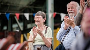 Man and woman are clapping they are standing in front of a string of coloured bunting