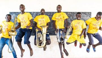 Group of six young people jumping in the air in front of a black board, holding brass instruments. They are wearing bright yellow t-shirts and jeans.