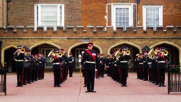Band members are standing in line on a forecourt in front of a red brick building