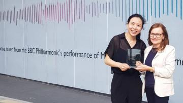 CJ Wu and BBE's Rosie standing in front of a large white backdrop with a soundwave. Rosie is wearing a white jacket and CJ is wearing black. They are both holding a clear rectangular plaque
