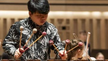 Boy playing a xylophone, holding three mallets in each hand