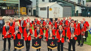 Hade Edge band stand in front of industrial buildings at the Coal Museum site. They are wearing red jackets and holding their instruments