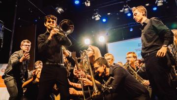 Group of young people holding brass instrumentsm they are all pointing towards a man playing the trombone