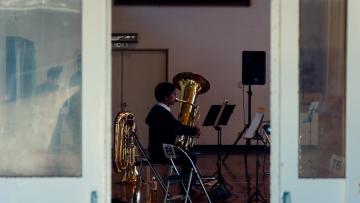 Man playing a brass instrument seen through an open door
