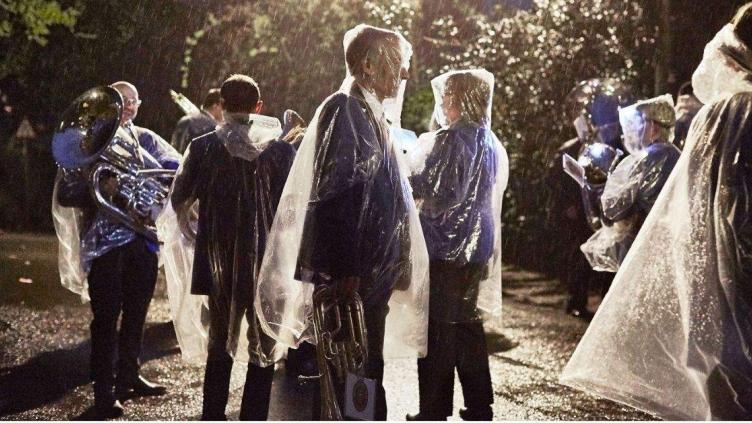 Group of people in rain at dusk are carrying brass instruments and wearing clear rain ponchos