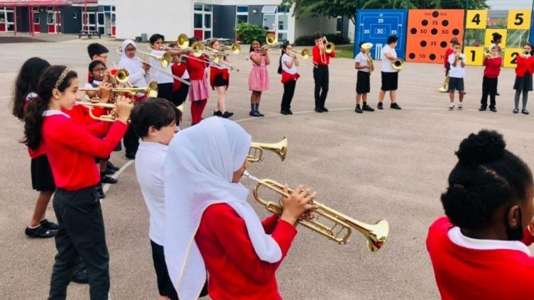 Children standing in a circle in a school tarmacked playground all playing a brass instrument