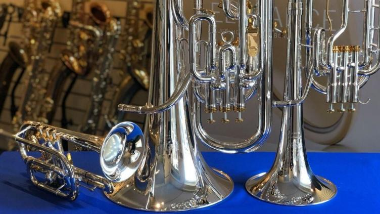 Upturned brass instruments on a table with blue cloth in front of a rack of saxophones
