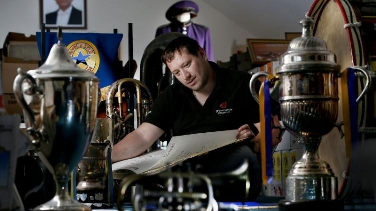 Man with brown hair and black polo top is reading a large score surrounded by trophies