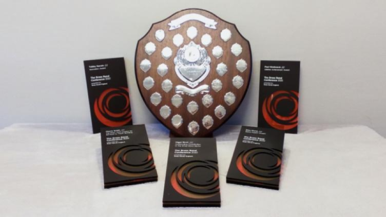 Large wooden shield covered in small engraved metal plaques, surrounded by five rectangular grey and orange awards