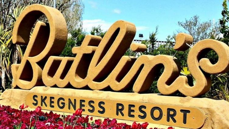 """Butlin's sign with giant cut-out letters sits behind a bed of poppies, sign also reads """"Skegness Resort"""""""