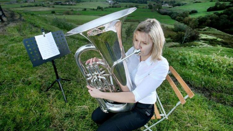 Woman is say on a wooden chair on a grassy hilltop, next to a music stand, she is playing a bass, she has blond hair and is wearing a white shirt and black trousers