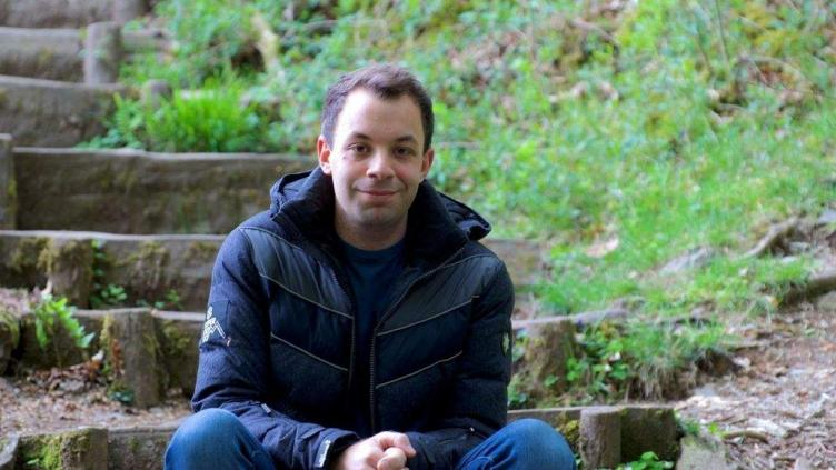 Sam is sitting on the bottom of a series of wooden steps next to a patch of grass he has brown hair and is wearing a navy blue coat and jeans