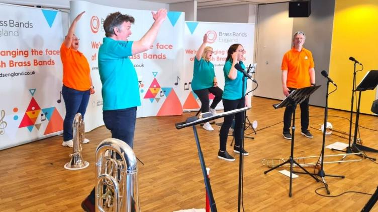 Five musicians each holding a brass instrument and wearing a different brightly coloured t-shirt are waving their arms in the air