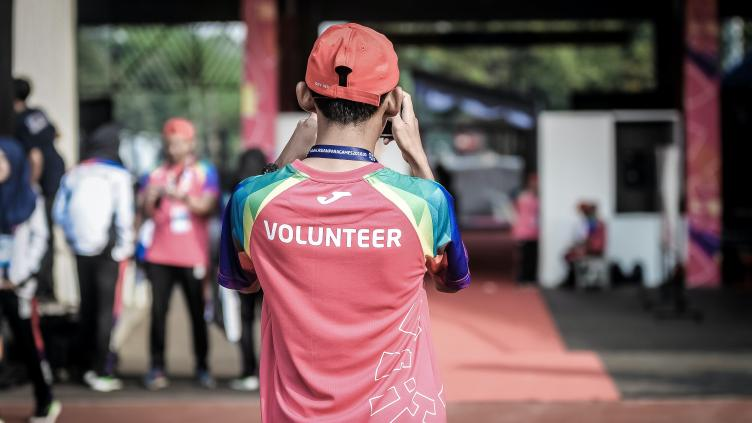 Person facing away from the camera, with a shirt with Volunteer printed on the back