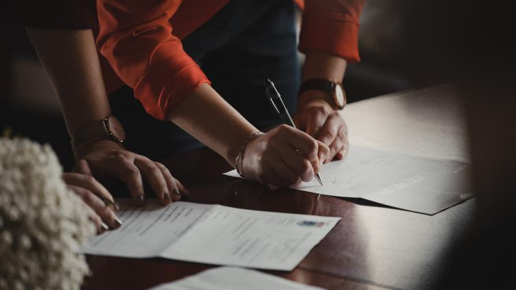 Someone signing a paper document