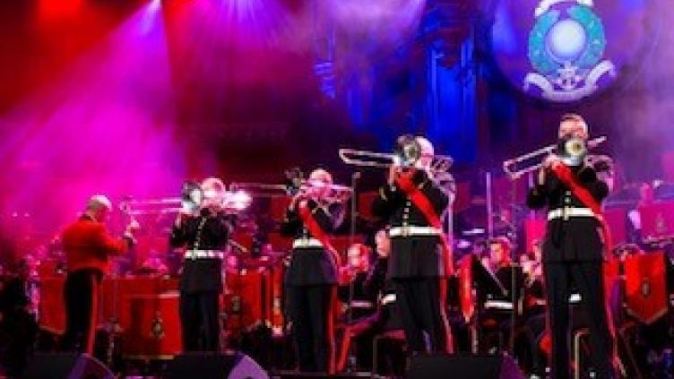 Line of marines standing on stage in uniform playing the trombone under a wash of pink and blue light
