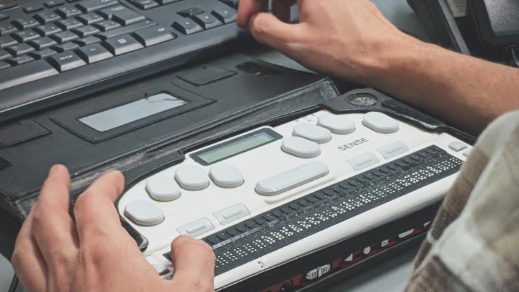 Someone using a Braille typewriter