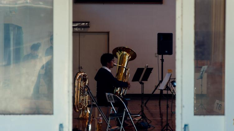 Man playing a brass instrument seen through an open door